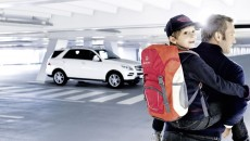 Red children's rucksack made from 100% polyester, for children aged 5 and over, S-shape shoulder straps, 3M reflectors, padded back section, pale grey Mercedes-Benz logo print on front, Deuter logo print on the shoulder strap, made by Deuter for Mercedes-Benz