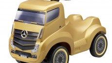 Gold-coloured ride-on Actros made from plastic. Ergonomic sitting position. Infinitely adjustable precision steering with small turning circle. Age 18 months+. Size: approx.: 59 x 30 x 45 cm. By Ferbedo for Mercedes-Benz. Item number B66004151. Price: 69.90 €
